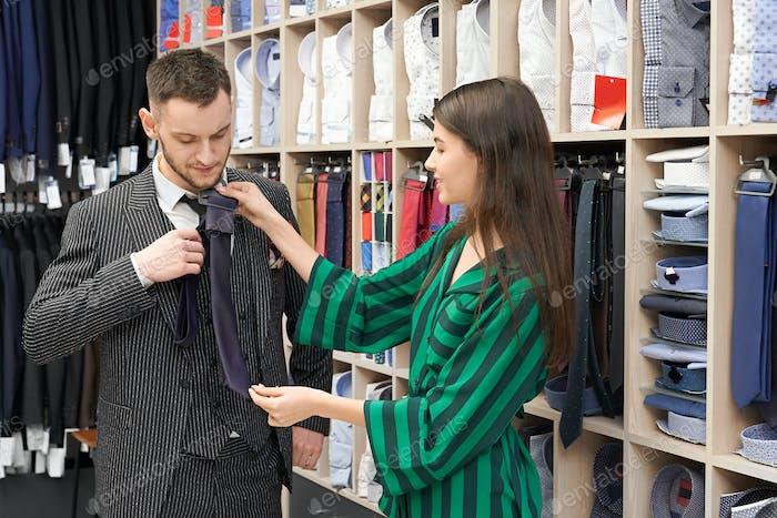 Gentleman in suit choosing cravat in fashionable boutique