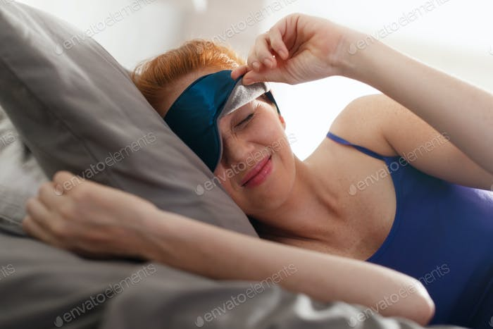 Woman In Bed With Sleep Mask On Eyes Waking Up