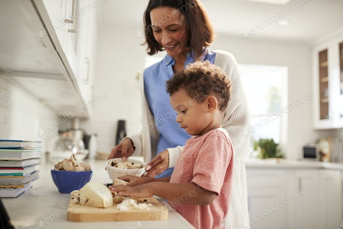 Millennial woman and her toddler son preparing food together standing in kitchen