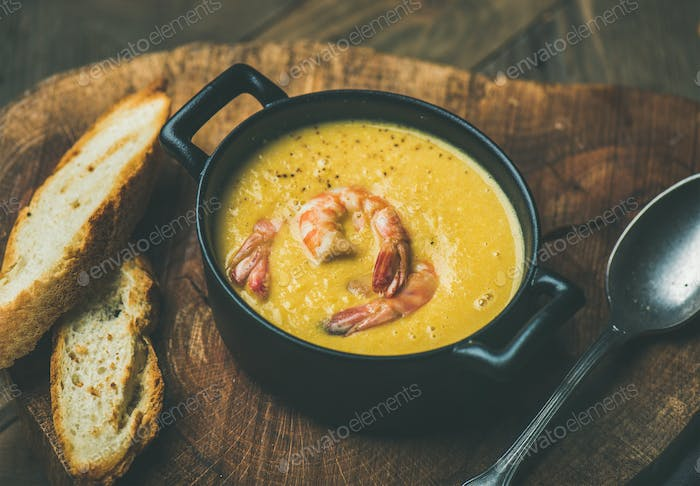 Corn creamy soup with shrimps served in pot