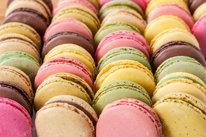Different colorful french macaroons in a rows.