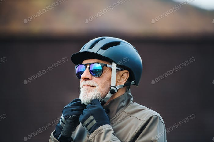An active senior man standing outdoors in town, putting on a bike helmet.