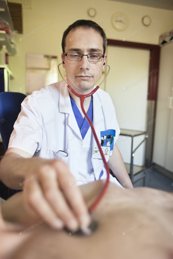 Doctor listening to heartbeat of patient through stethoscope in hospital
