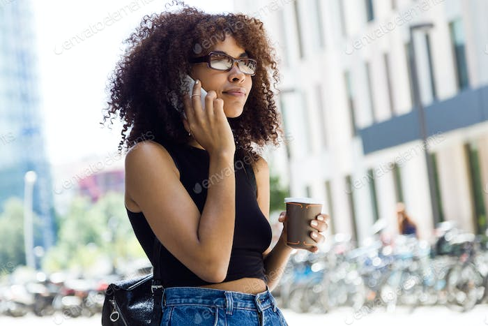 Beautiful young woman using her mobile phone in the street.