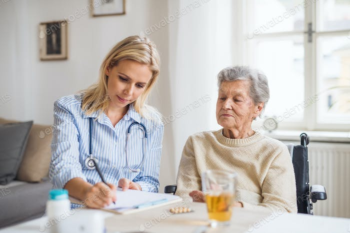 A health visitor explaining a senior woman in wheelchair how to take pills.