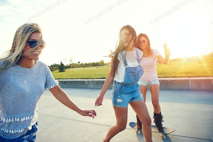 Beautiful friends play outside on skate boards