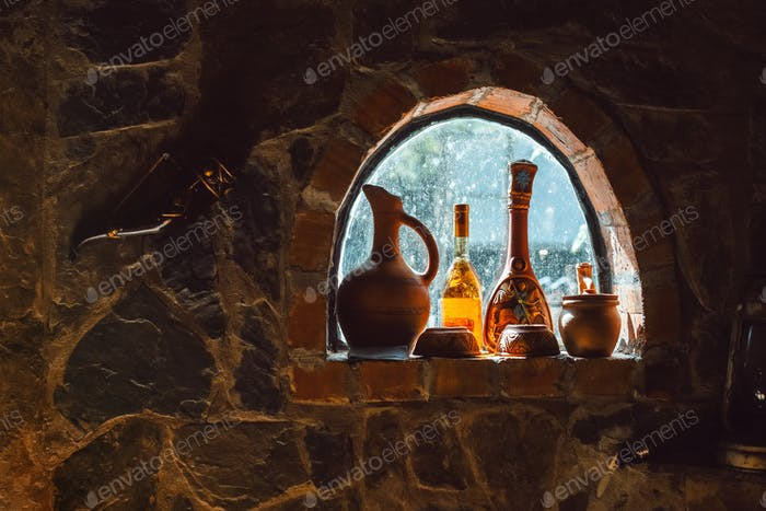Old rustic wine bottles, jugs on a small cellar window on a stone wall