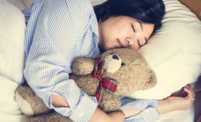 A woman in bed with a teddy bear