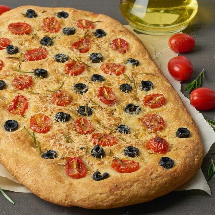 Focaccia, pizza, italian flat bread with tomatoes, olives and rosemary on brown table, side view