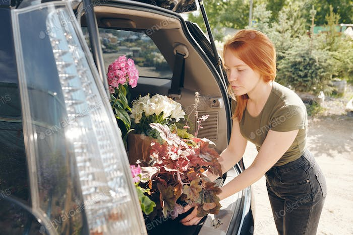 Redhead florist putting flowers in trunk