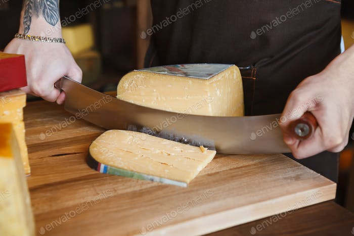 Cutting hard cheese in grocery shop