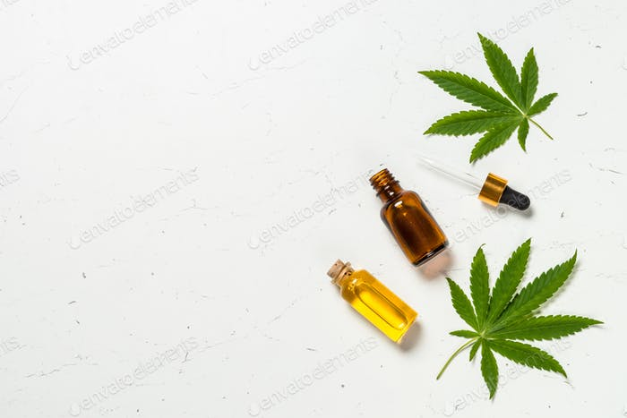 Cannabis oil and green leaves at white table