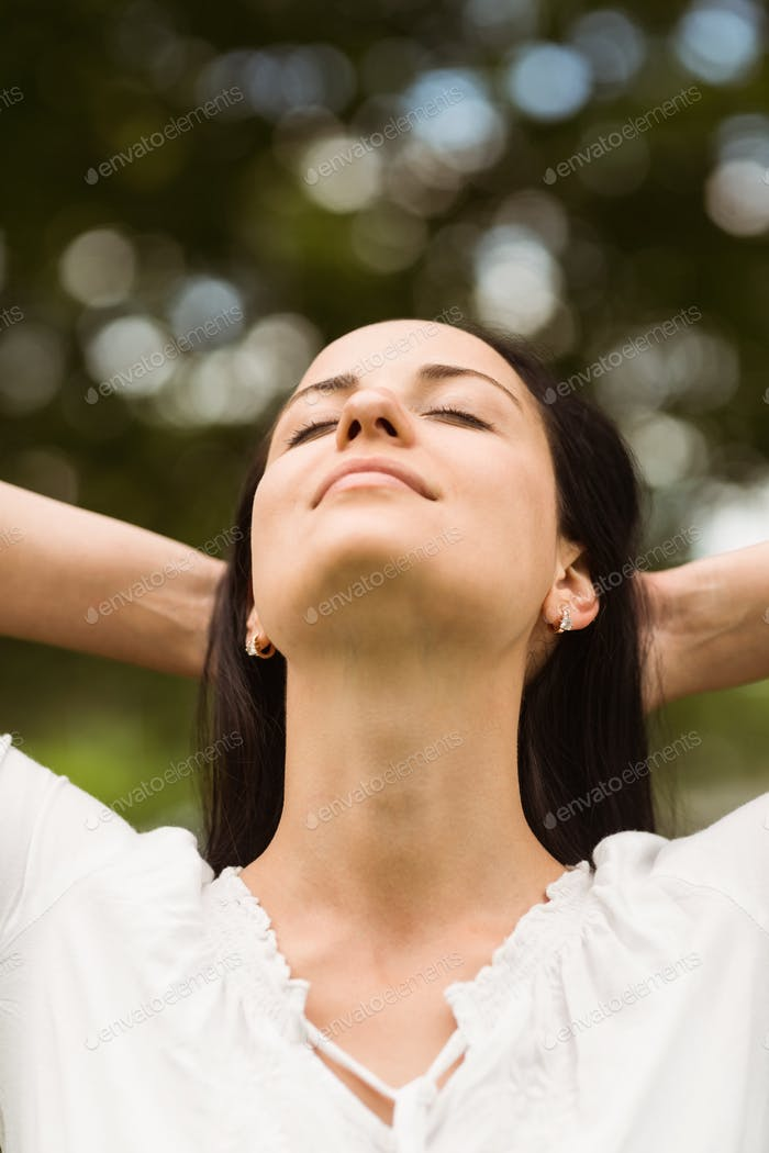 Brunette enjoying nature with her hands behind head in the park