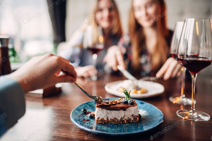 Young women eats sweet cakes in restaurant