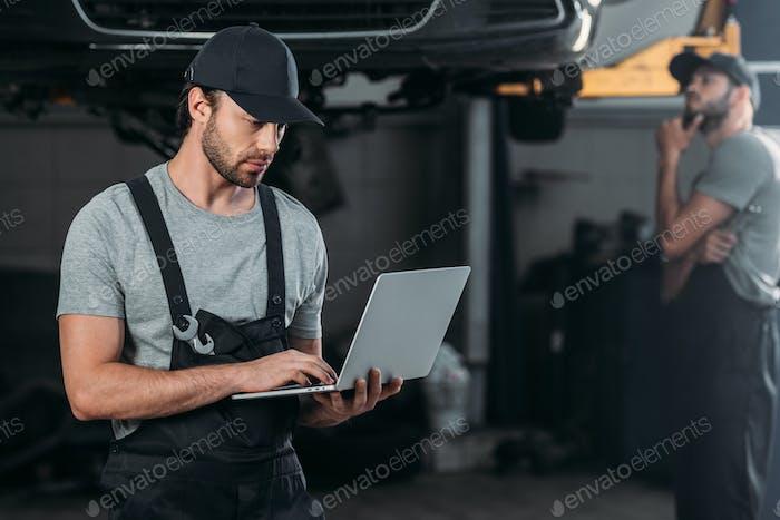 Automechaniker mit Laptop, während Kollege in der Werkstatt hinter