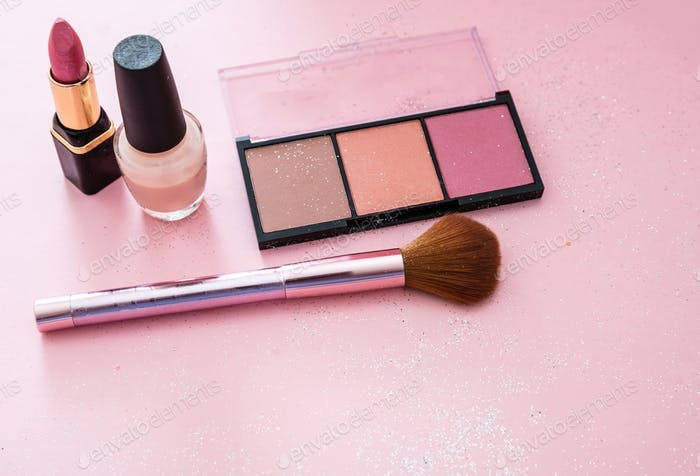 Blush powder and brush, lipstick and nail polish against pink background
