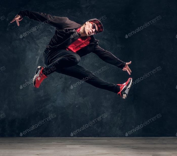 Emotional stilvoll gekleideter Kerl Durchführung Break Dance Springen.