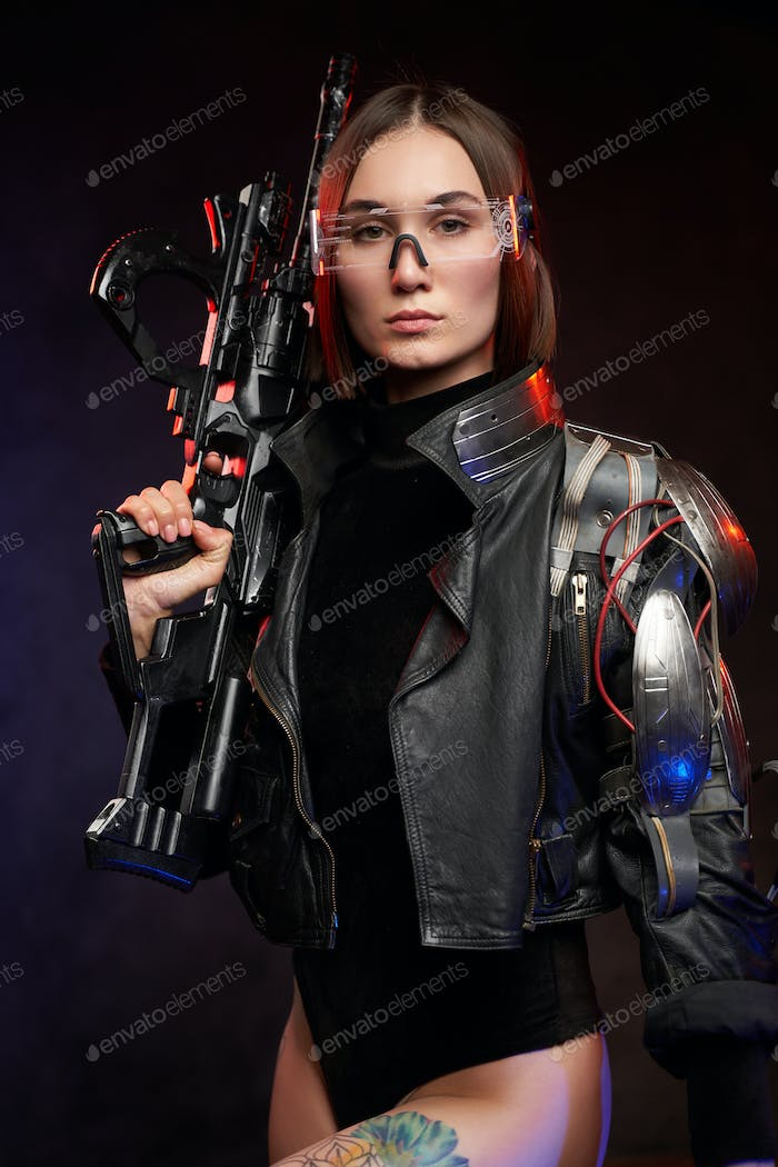 Serious and beautiful female soldier with rifle in dark background