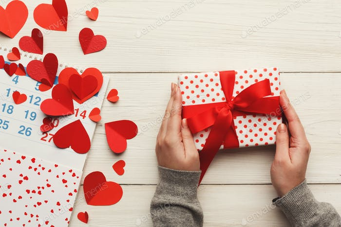 Valentine day background, gift box and hearts on white wood