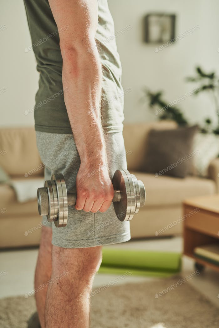 Middle section of young sportsman in activewear exercising with barbells
