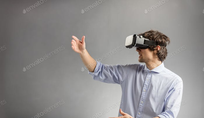 Young man playing in virtual reality goggles