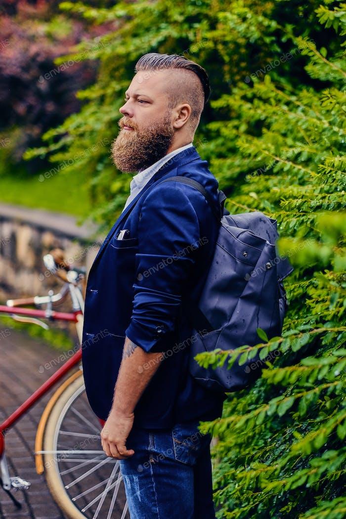 Стильный бородатый мужчина с рюкзаком в городском парке.