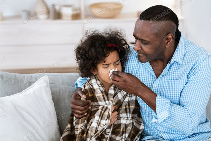 Viral disease treatment. Loving grandfather treating his unhealthy granddaughter at home, copy space