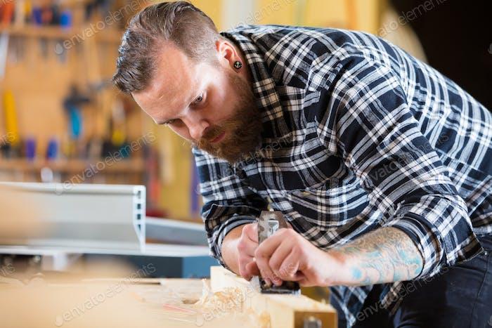 Tischler arbeitet mit Flugzeug auf Holzdiele in der Werkstatt