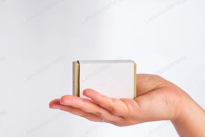Manos de mujer sosteniendo una barra de jabón de oliva en paquete maqueta