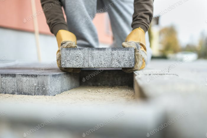 Man laying a paving brick placing it on the sand foundation