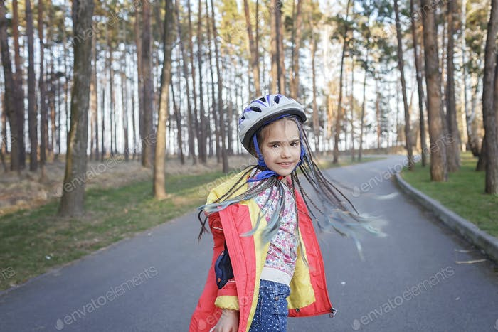 Happy kid in sport helmet riding on roller skates at park, spring family activity, outdoors