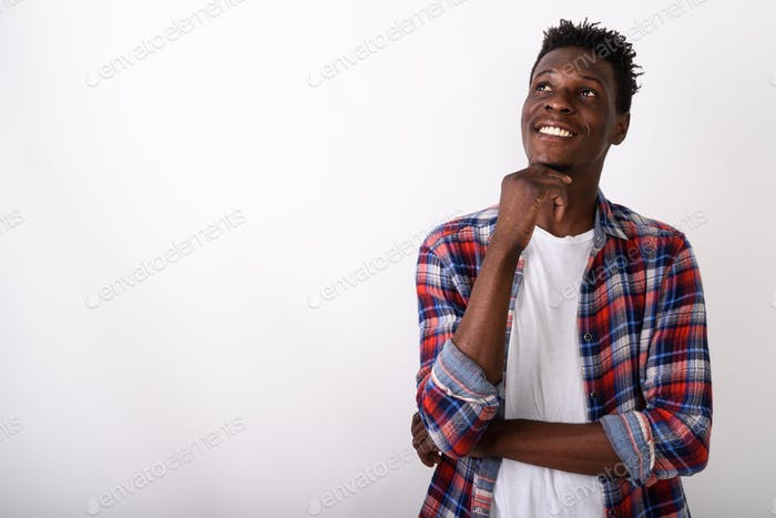 Studio shot of young happy black African man smiling and thinkin