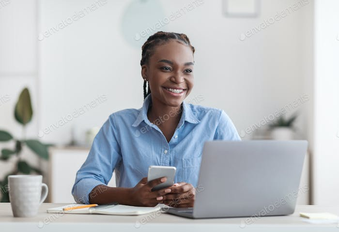 Self-Employment. Joyful Black Millennial Woman Sitting At Workplace In Home Office