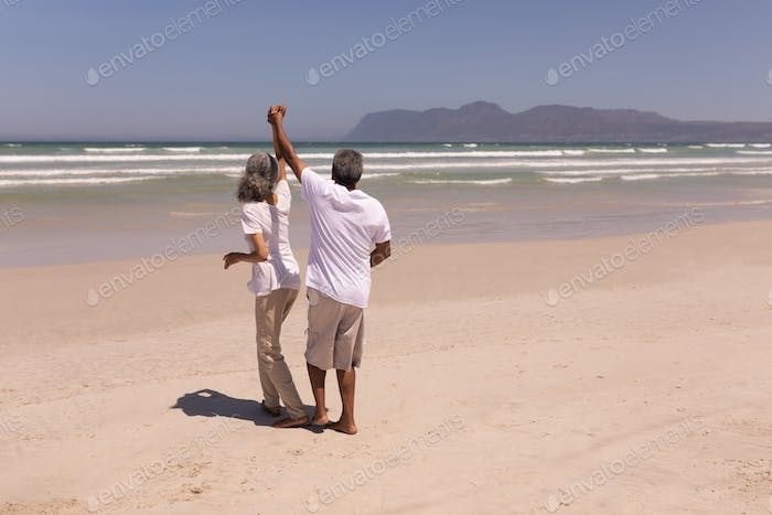 Rear view of happy senior couple dancing together on beach in the sunshine