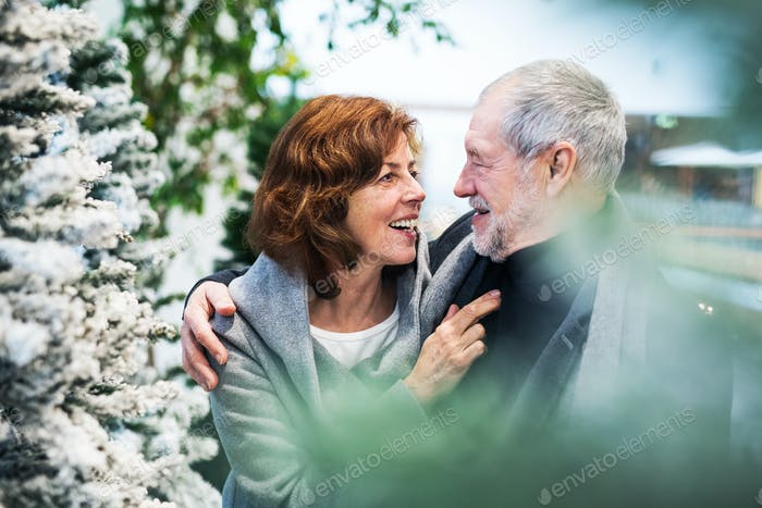 A portrait of senior couple in shopping center at Christmas time.