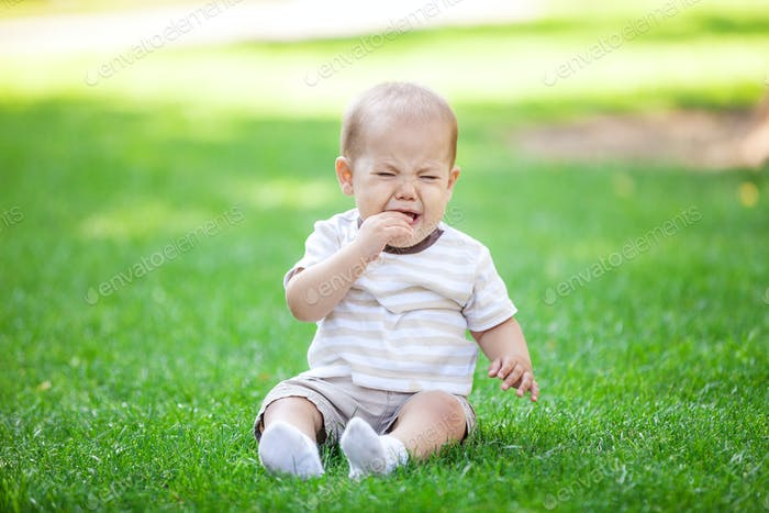 Little boy crying while sitting on grass in park