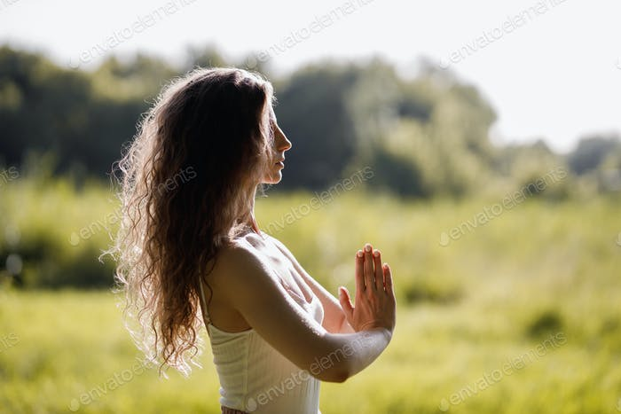 Young woman in yoga clothes is practising yoga in the open air in the forest on the sunny day