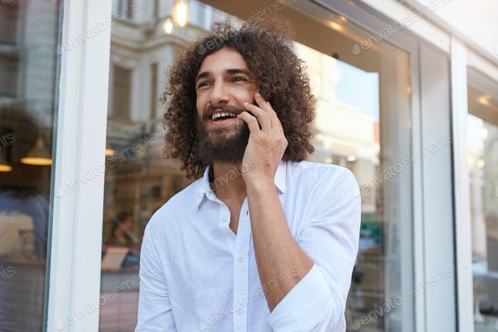 Happy curly bearded guy walking down street and having pleasant talk on his phone