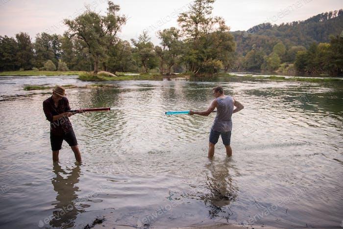 young men having fun with water guns