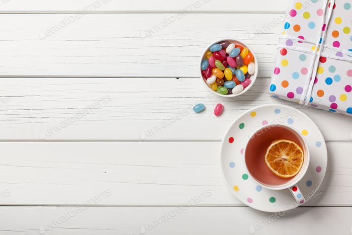 Gift box, cup of tea and colorful candies on white wooden background
