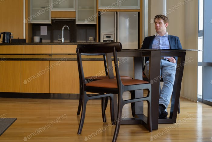 Young handsome businessman sitting in the dining room near the k
