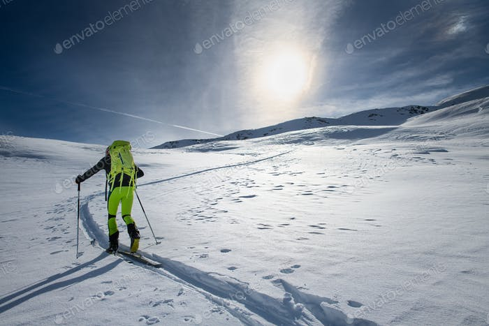 Mountaineer skier alone on a marked slope