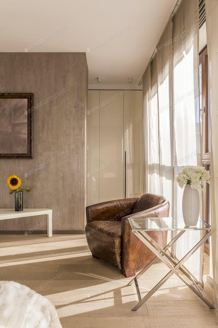 Vintage armchair and flowers in room