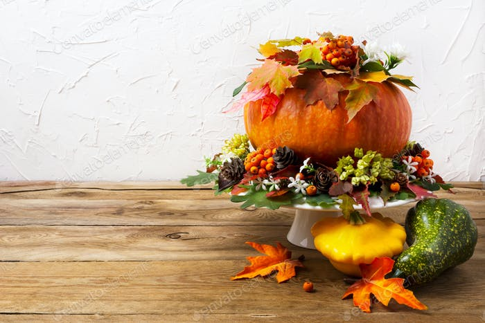 Thanksgiving table centerpiece with pumpkin and yellow squash, c