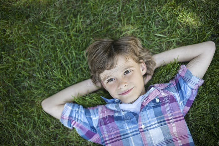 A boy lying on the grass, hands behind his head.