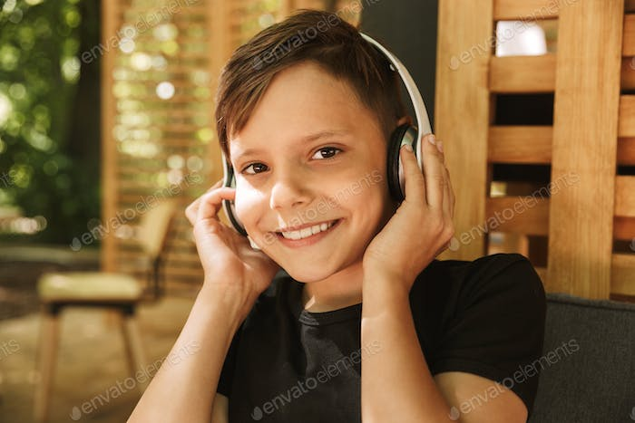 Cheerful boy sitting in cafe nature listening music