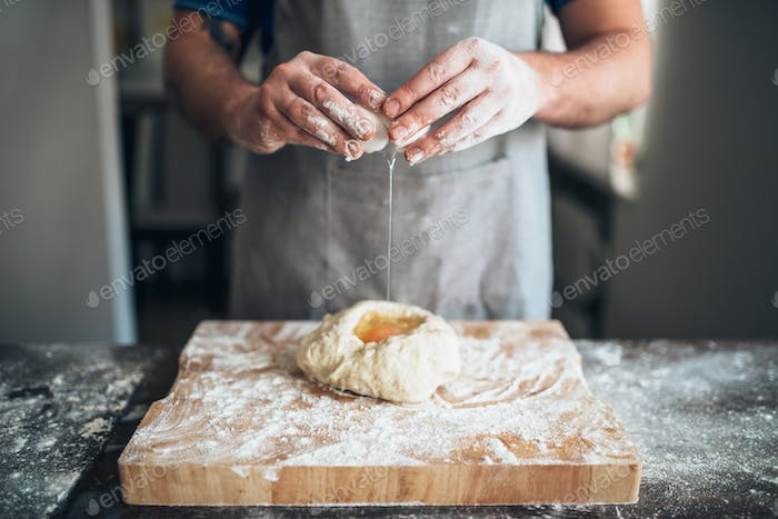 Chef hands mix dough with egg, bread preparation
