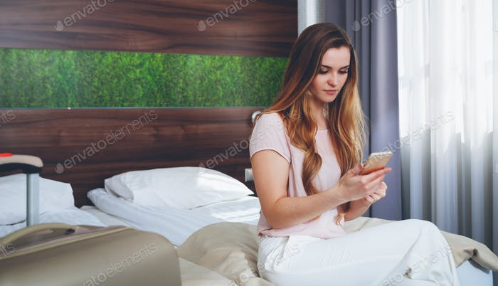 Pretty woman with suitcase in modern hotel apartment using phone