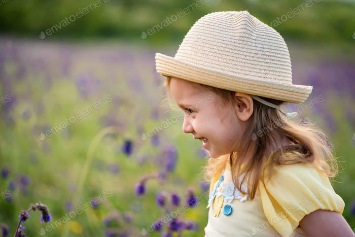 Cute smiling baby girl in beige hat outdoors in green field. Child portrait