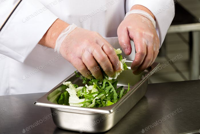 Cooking food. The hands of the chef make a salad